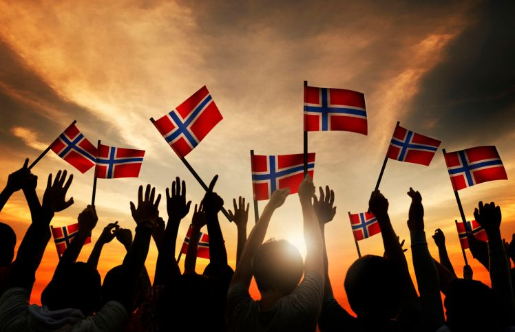 31310464 - group of people waving norwegian flags in back lit